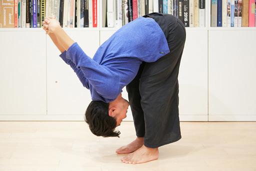 立ち姿勢で後ろで手を組み、膝を少し曲げながら前屈。首の力を抜く。
