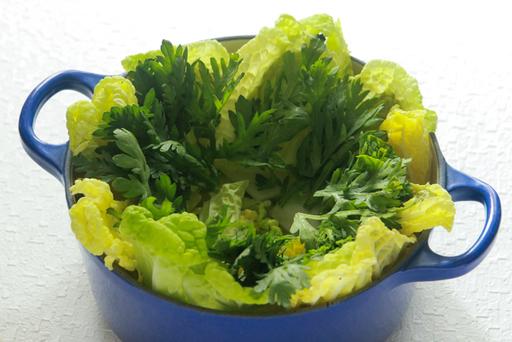 鍋をふちどるように、白菜の葉先と春菊をしいて