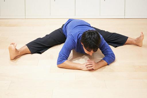 開脚した状態で少しずつからだを前に倒していく。クッションなどを置いて、抱えるようにからだを倒すとやりやすい。