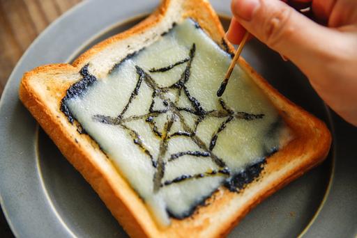 余ったイカ墨ソースでクモの巣模様を描く
